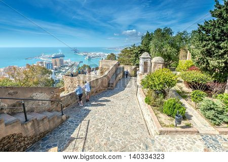 Malaga, Andalucia, Spain - April 16, 2016: people observe the panoramic view of port of Malaga from the Gibralfaro Castle.