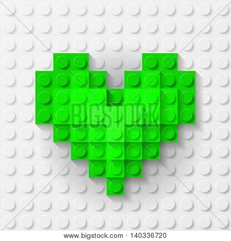 Plastic green heart on white background made of construction kit