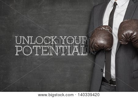 on blackboard with businessman wearing boxing gloves