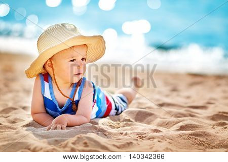one year old boy lying the beach in straw hat. Child resting at the sea