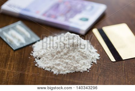 drug use, crime, addiction and substance abuse concept - close up of crack cocaine drug dose track on mirror with credit card and money