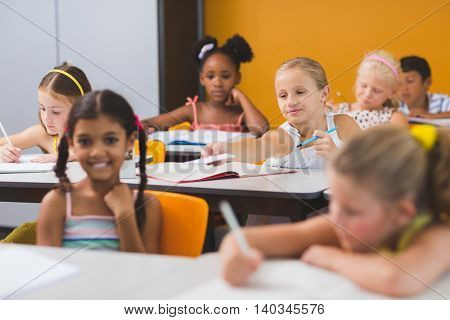 Schoolgirl giving chit to her friends in classroom at school