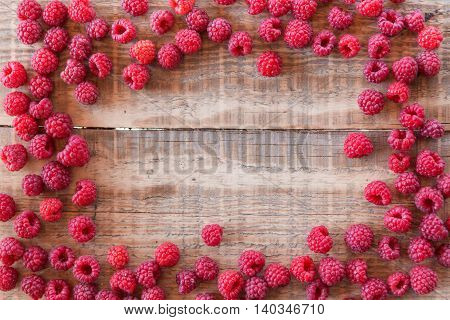 red rasberry in sunlight on wooden background