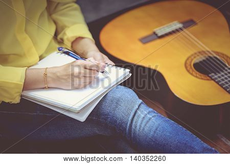 Closeup Songwriter Writing On Note Paper With Acoustic Guitar Near By. Vintage Tone.