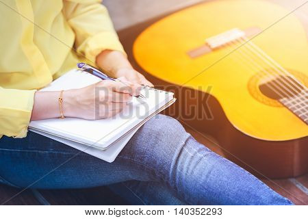 Closeup Songwriter Writing On Note Paper With Acoustic Guitar Near By.