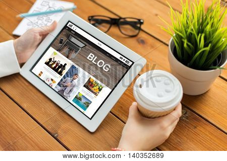 business, technology, media, internet and people concept - close up of woman with blog web page on tablet pc computer screen drinking coffee on wooden table