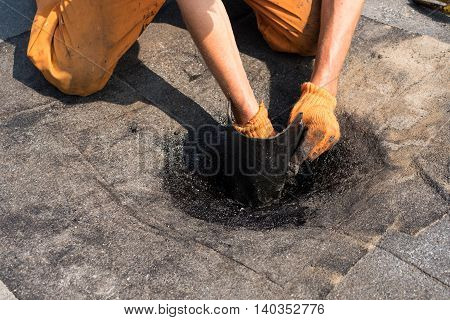 Roofer doing repair roof drain. Flat roof installation. Heating and melting bitumen roofing felt. Flat roof repairing with roofing felt. Professional master making waterproofing.