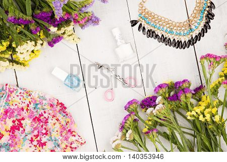 Dress, Colorful Flowers, Cosmetics Makeup, Bijou And Essentials On White Wooden Background
