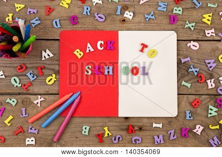 "School Set With Inscription Of ""back To School"", Wooden Letters, Notepad And Crayons On Brown Wooden"