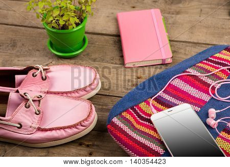 Colorful Bag, Smart Phone, Headphones, Notepad And Pink Shoes On Wooden Desk