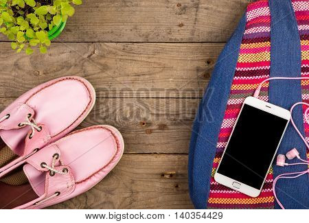 Colorful Bag, Smart Phone, Headphones And Pink Shoes On Wooden Desk