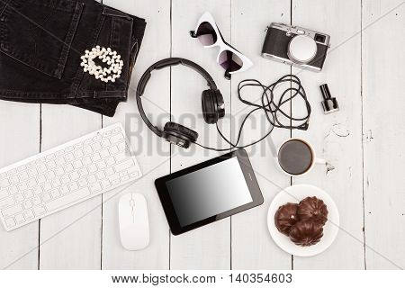 Jeans, Tablet Pc, Camera, Headphones, Computer Keyboard, Sunglasses And Coffee On White Wooden Desk