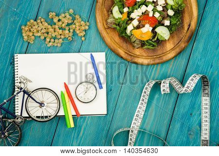 Bicycle Model, Salad Of Fresh Vegetables, Notepad, Stopwatch And Tape Measure On A Blue Wooden Table