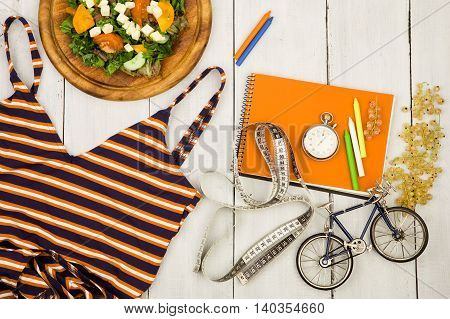 Bicycle Model, Swimsuit, Salad Of Fresh Vegetables, Orange Notepad, Stopwatch And Tape Measure On A