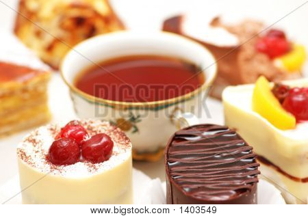 Selection Of Sweet Cakes And Tea On The Table