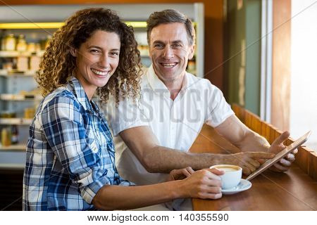 Portrait of happy couple using digital tablet while having coffee in a café