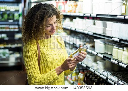 Woman selecting a bottle of oil in a super market
