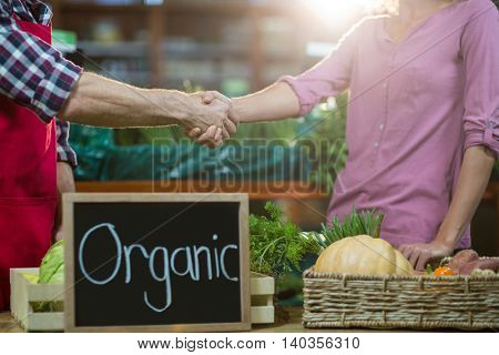 Mid-section of staff shaking hand with woman in organic section of supermarket