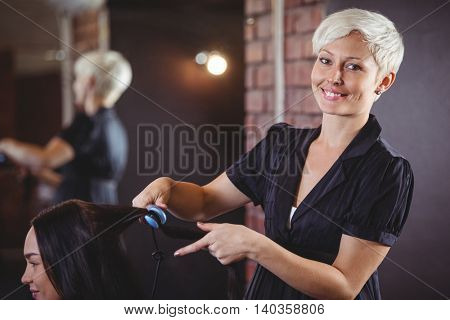 Portrait of female hairdresser straightening the hair of a client at a salon