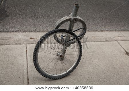 Wheel from a bicycle shackle lock to the post. The rest is stolen