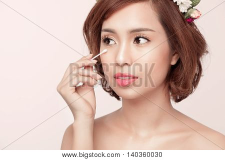 Young beauty in robe removing eyes make-up. Facial closeup of happy smiling beautiful asian woman.