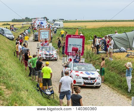 QuievyFrance - July 07 2015: Carrefour Caravan during the passing of the Publicity Caravan on a cobblestoned road in the stage 4 of Le Tour de France on July 7 2015 in Quievy France.
