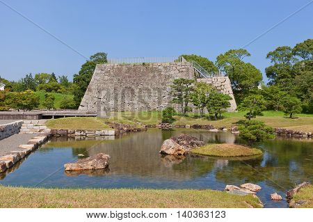 AKO JAPAN - JULY 18 2016: Pond and stone base of main keep (donjon or Tenshu) in main bailey of Ako Castle (circa 17th c.) in Ako Japan. Castle was a seat of Lord Asano Naganao