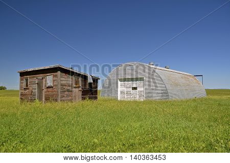 Old wood shed and steel shed surrounded by long grass on the prairie
