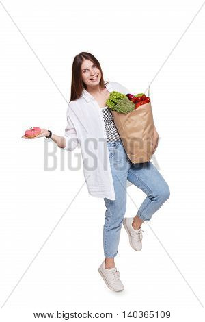 Happy young woman holding shopping paper bag full of groceries, vegetables and fruits and glazed donut, isolated at white background. Healthy food shopping. Female buyer came from market