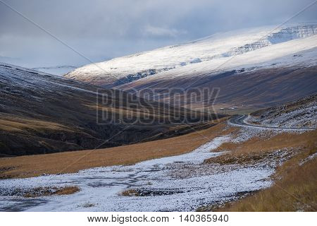 Beautiful snowcapped mountain yellow field and cloudy sky - scenic landscape in early winter of Iceland