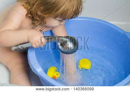 Small cute funny baby boy with blonde hair playing with rubber yellow duckling toy in bath water