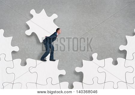 businessman struggling to complete a jigsaw puzzle alone