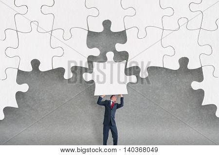 business challenge concept businessman completing a jigsaw puzzle