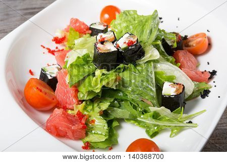 Fusion salad with grapefruits, iceberg lettuce and japanese rolls