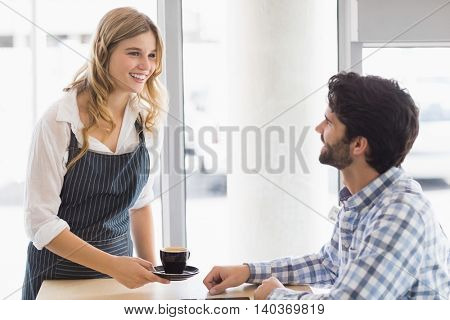 Smiling waitress serving a coffee to customer in cafe