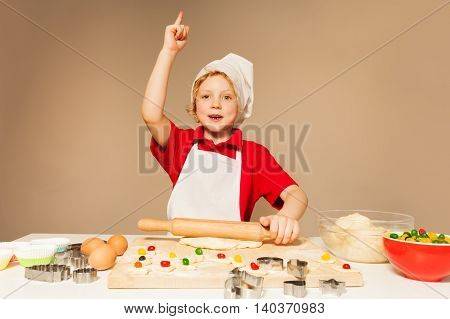 Cute kid boy in baker's uniform flattening dough with wooden rolling pin for candy filled cookies, pointing up.