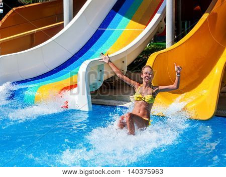 Child on water slide at aquapark show thumb up. There are some water slides with flowing water in aqua park. Summer water park holiday. Outdoor. Summer freedom.