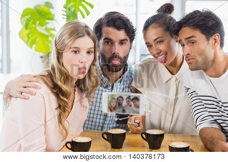 Group of happy friends taking picture with slefie stick in cafe