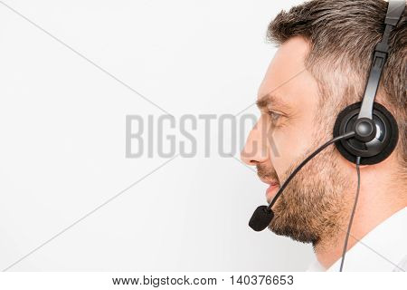 Side View Of Smiling Operator Of Call Center In Headphones