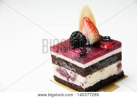 A slice of delicious black forest cake garnished with berry