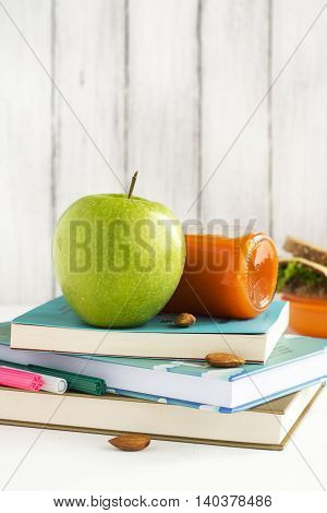 School lunchbox: healthy food, fruits, books and apple over white table. Selective focus