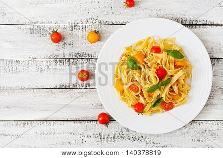 Fettuccine Pasta In Tomato Sauce With Chicken, Tomatoes Decorated With Basil On A Wooden Table. Top