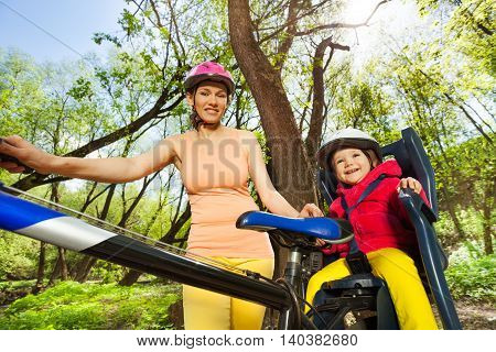 Little toddler girl in bicycle helmet sitting in  bike seat outdoors with her sporty mother