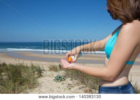 Sunscreen woman putting solar cream or sunblock smiling happy in bikini by ocean