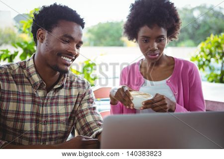 Young couple using laptop while having coffee in cafeteria