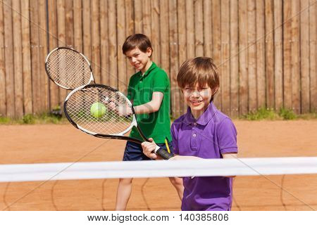 Two young tennis players, ten years old friends or brothers hitting the ball outside in summer