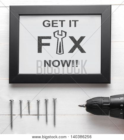 Fix call us now text on black frame with nails and screwdriver. Repair service poster on wooden background. Power drill with screws