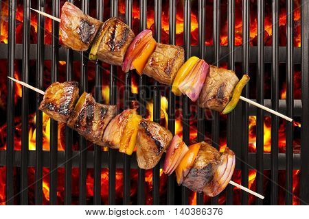 Top view of red meat skewers being grilled in a barbecue.