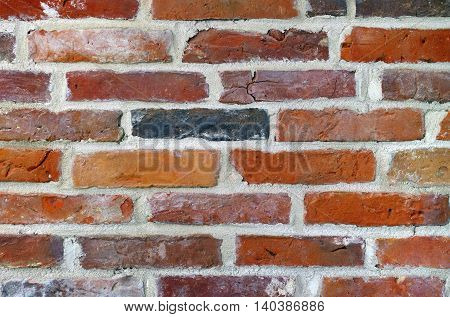 Ancient red bricks used to build up a new wall.