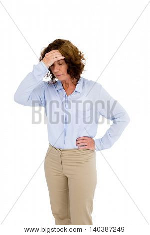 Mature woman touching head while standing against white background